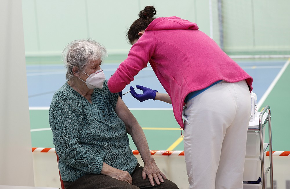 An elderly woman receives Moderna COVID-19 vaccine at a sports hall in Ricany, Czech Republic, Friday, Feb. 26, 2021. With new infections soaring due to a highly contagious coronavirus variant and hospitals filling up, one of the hardest-hit countries in the European Union is facing inevitable: a tighter lockdown. (AP Photo/Petr David Josek)