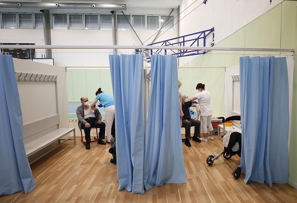 V pátek 26. února 2021 dostávají starší lidé vakcínu Moderna Kovit-19 ve sportovní hale v Rikini v České republice.  S nákazlivou variantou viru korona a nemocnicemi dochází k nárůstu nových infekcí, což z ní činí jednu z nejzranitelnějších zemí, kterým EU nevyhnutelně čelí: přísné zamykání.  (AP Photo / Peter David Josek)