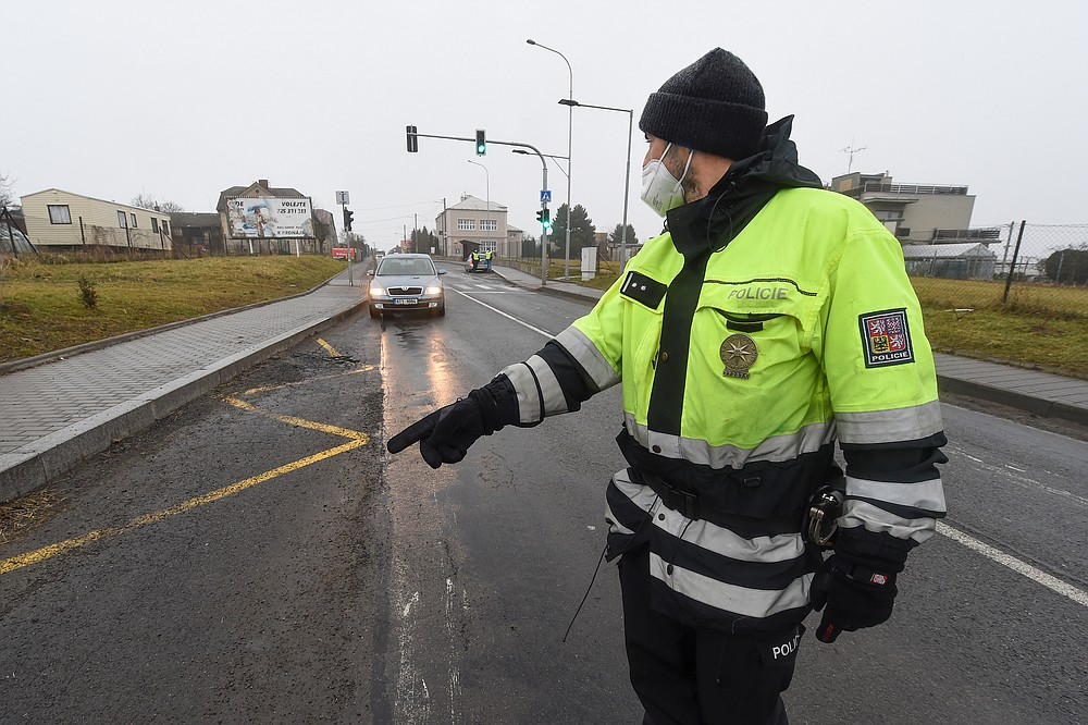 A police officer stops a car on a road between the towns, Ostrava and Opava, near Dehylov, Czech Republic Monday, March 1, 2021. Limits for free movement of people are set in the Czech Republic. Travelling to other counties unless the go to work or have to take care about relatives is prohibited. (Jaroslav Ozana/CTK via AP) ** SLOVAKIA OUT **