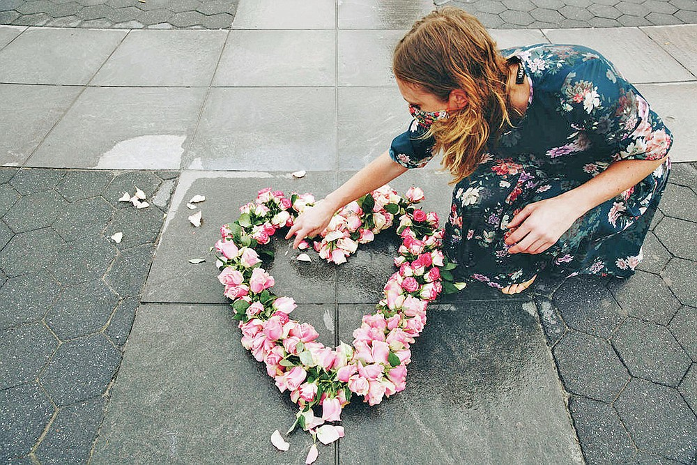 In this Aug. 27, 2020 photo, artist Kristina Libby constructs a floral heart in New York City's Washington Square Park to honor the victims of COVID-19. Libby realized that the community had no physical space to mourn, so she began her project of laying floral hearts across the city. (Erica Reade via AP)