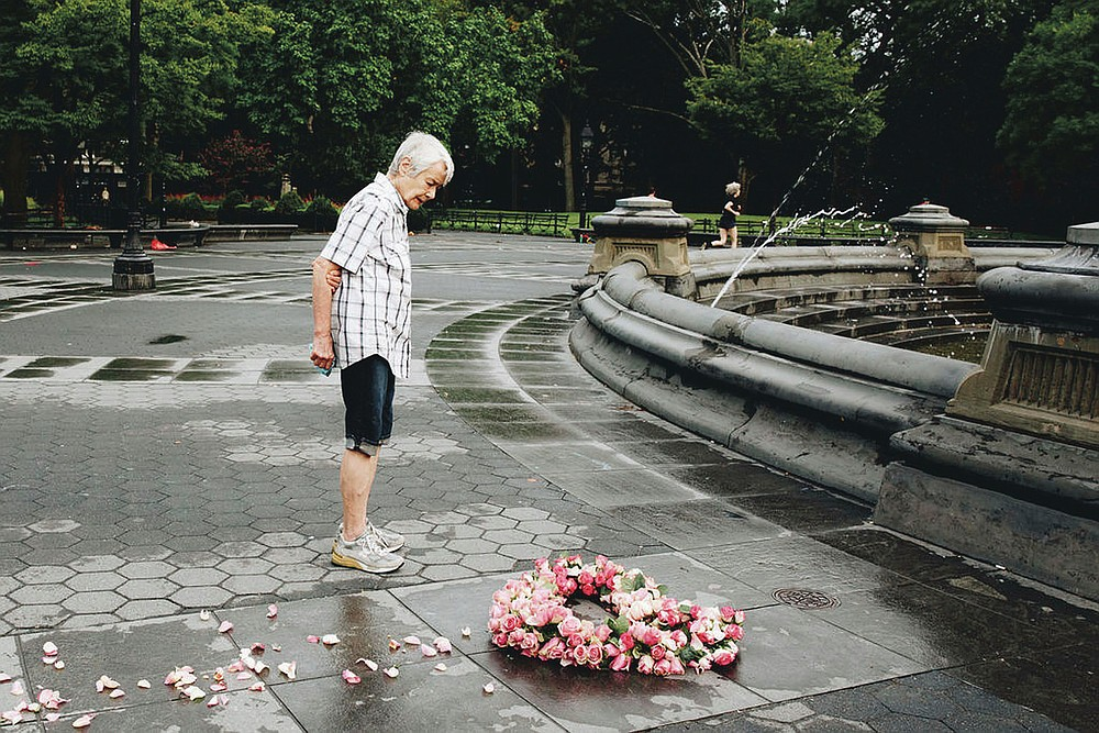 In this Aug. 27, 2020 photo, a man stops to look at a floral heart honoring the victims of COVID-19 that was made by artist Kristina Libby in New York City's Washington Square Park. Libby realized that the community had no physical space to mourn, so she began her project of laying floral hearts across the city. (Erica Reade via AP)