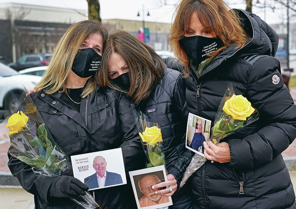 From left, Michelle Pepe, Lisa Post Mazerolle and Jill Federman hold photos of each of their fathers as they mourn, Monday, March 1, 2021, in Lynnfield, Mass. When artist Kristina Libby started the Floral Heart Project to give the survivors of COVID-19 victims places to mourn, she was thinking of people like these three woman who lost their fathers in April, 2020 and who were unable to see them in their last moments. (AP Photo/Elise Amendola)