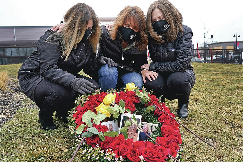 From left, Michelle Pepe, Jill Federman and Lisa Post Mazerolle mourn their respective fathers, Monday, March 1, 2021, in Lynnfield, Mass. When artist Kristina Libby started the Floral Heart Project to give the survivors of COVID-19 victims places to mourn, she was thinking of people like these three woman who lost their fathers in April, 2020 and who were unable to see them in their last moments. (AP Photo/Elise Amendola)