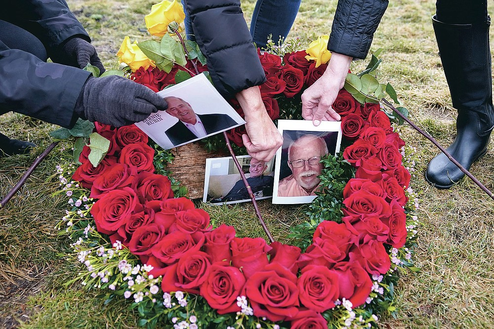From left, Michelle Pepe, Jill Federman and Lisa Post Mazerolle place photos of their fathers onto an array of heart-shaped roses, Monday, March 1, 2021, in Lynnfield, Mass. When artist Kristina Libby started the Floral Heart Project to give the survivors of COVID-19 victims places to mourn, she was thinking of people like these three woman who lost their fathers in April, 2020 and who were unable to see them in their last moments or have proper funerals. (AP Photo/Elise Amendola)