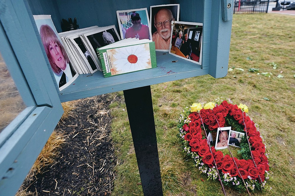 Photos of loved ones are seen on a floral arrangement and wooden box, Monday, March 1, 2021, in Lynnfield, Mass. When artist Kristina Libby started the Floral Heart Project to give the survivors of COVID-19 victims places to mourn, she was thinking of people who lost their loved ones and who were unable to see them in their last moments nor have funeral services. (AP Photo/Elise Amendola)