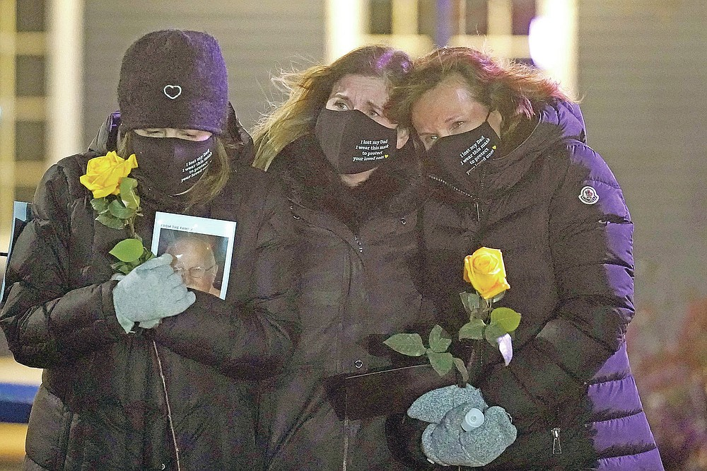 From left, Lisa Post Mazerolle, Michelle Pepe and Jill Federman mourn their respective fathers, Monday, March 1, 2021, in front of the Medfield Town Hall, in Medfield, Mass. The three women, who all lost their fathers due to COVID-19 within days of each other, placed three separate floral hearts in different towns in the Boston metro area throughout the day Monday. (AP Photo/Steven Senne)