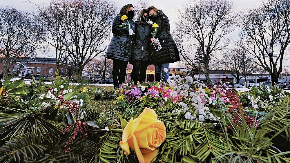 Lisa Post Mazerolle, Michelle Pepe and Jill Federman, from left, mourn together after laying a wreath in memory of their fathers, during a ceremony on the town common, Monday, March 1, 2021, in Natick, Mass. When artist Kristina Libby started the Floral Heart Project to give the survivors of COVID-19 victims places to mourn, she was thinking of people like these three women who lost their fathers in April 2020 and who were unable to see them in their last moments. (AP Photo/Charles Krupa)