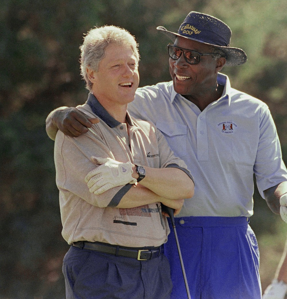 FILE- In this Aug. 22, 1993 file photo, President Bill Clinton is consoled by White House adviser and golf partner Vernon Jordan after Clinton hit a bad shot during their golf match at the Farm Neck Golf Club in Oak Bluffs, Mass., on Martha's Vineyard.  Jordan, who rose from humble beginnings in the segregated South to become a champion of civil rights before reinventing himself as a Washington insider and corporate influencer, died Tuesday, March 2, 2021, according to a statement from his daughter. He was 85. (AP Photo/Marcy Nighswander, File)