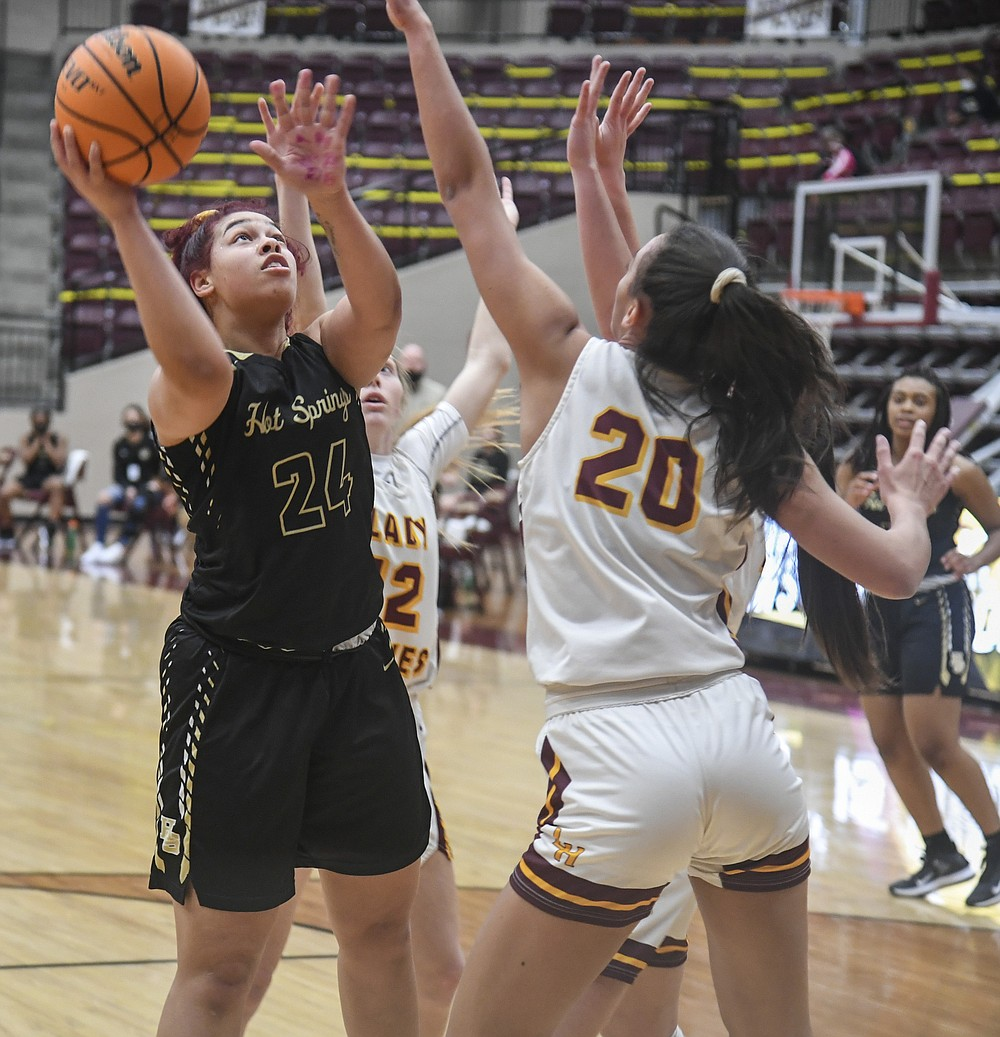 Hot Springs' Jurnee Hicks (24) takes a shot while under pressure from Lake Hamilton's Audri Winfrey (20) in Tuesday's game at Wolf Arena. - Photo by Grace Brown of The Sentinel-Record