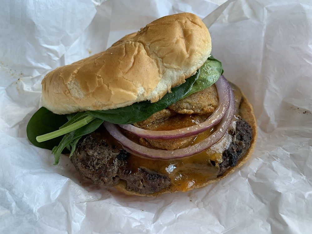 Backyard Burgers' Honey BBQ Burger puts a hefty charcoal-grilled patty, honey barbecue sauce, fried pickles, cheese, red onions and greenery on a brioche-style bun. (Arkansas Democrat-Gazette/Eric E. Harrison)
