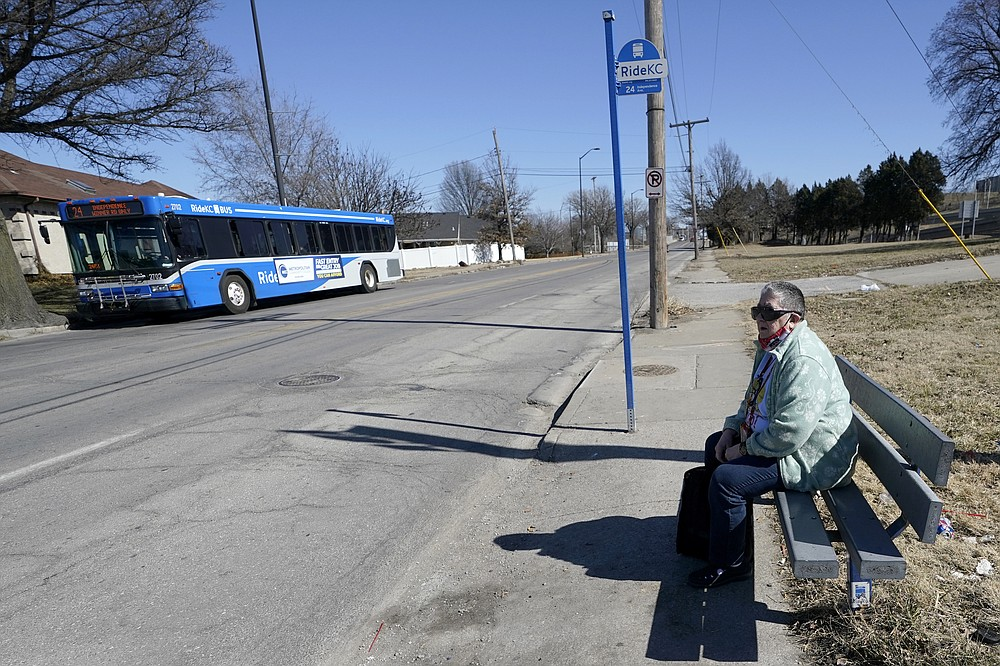 Pat Brown waits at a bus stop in Kansas City, Mo., Wednesday, March 3, 2021. Brown knows she needs the vaccine because her asthma and diabetes put her at higher risk of serious COVID-19 complications. But Brown hasn't attempted to schedule an appointment and didn't even know if they were being offered in her area yet; she says she is too overwhelmed. (AP Photo/Orlin Wagner)