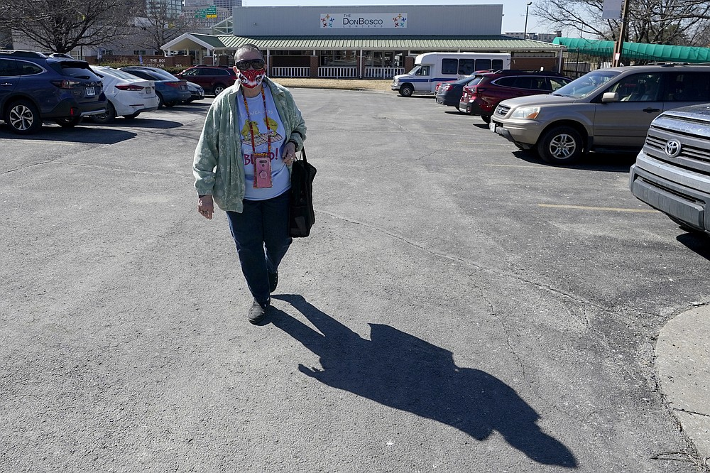 Pat Brown walks away from the Don Bosco Senior Center in Kansas City, Mo., Wednesday, March 3, 2021. Brown knows she needs the vaccine because her asthma and diabetes put her at higher risk of serious COVID-19 complications. But Brown hasn't attempted to schedule an appointment and didn't even know if they were being offered in her area yet; she says she is too overwhelmed.  (AP Photo/Orlin Wagner)