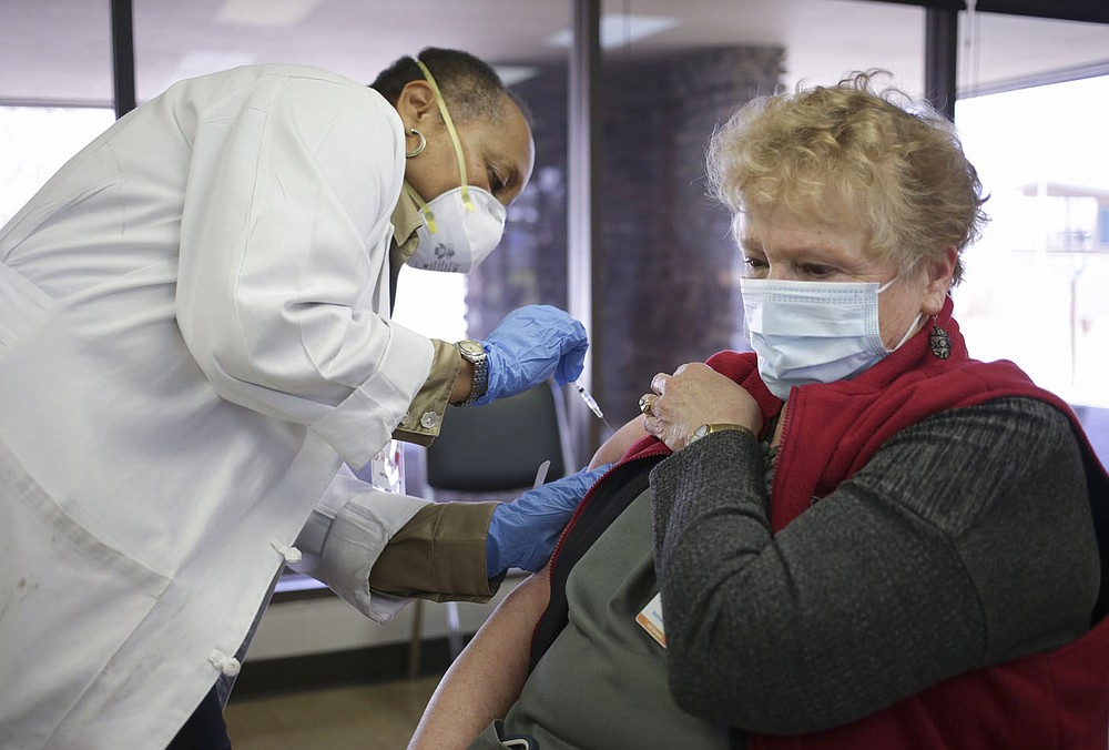 Dr. Glenda Patterson(from left) administers a covid-19 vaccine to Care Butler of Bella Vista, Thursday, March 4, 2021 at Riordan Hall in Bella Vista. The Bella Vista Fire Department with the help of volunteers held a vaccine clinic for people in Phase 1-B. They planned 1,200 first doses for the one-day event.(NWA Democrat-Gazette/Charlie Kaijo)