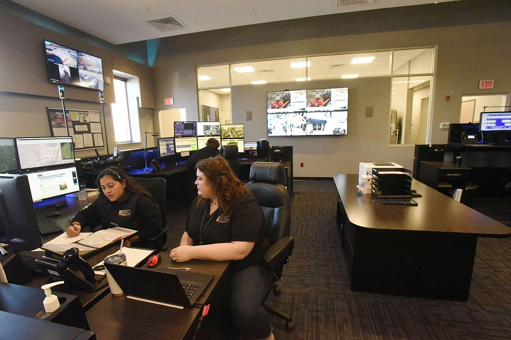 Amanda Aristondo (left) and Kiersten Hayes (both cq) go over data on Tuesday March 2 2021 while on duty at the Bentonville Police Department communications center. A new radio system for the department is part of a $266 million bond issue residents will vote on on April 13. (NWA Democrat-Gazette/Flip Putthoff)