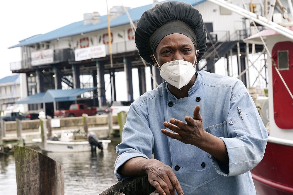 Leo Carney, kitchen manager at McElroy's Harbor House in Biloxi on the Mississippi Gulf Coast, stands along the dock at the city's small craft harbor on Friday, March 5, 2021, as he speaks about his belief that the removal of coronavirus restrictions will disproportionately impact Black residents — many of whom are essential workers. Carney said he would feel better with restrictions being removed if essential workers had access to the coronavirus vaccine. (AP Photo/Rogelio V. Solis)