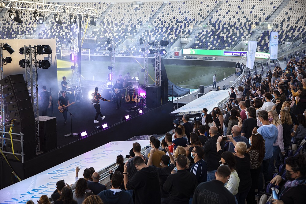 "Israeli musician Ivri Lider performs in front of audience, where all guests were required to show ""green passport"" proof of receiving a COVID-19 vaccination or full recovery from the virus at a soccer stadium in Tel Aviv, Friday, March. 5, 2021. (AP Photo/Oded Balilty)"