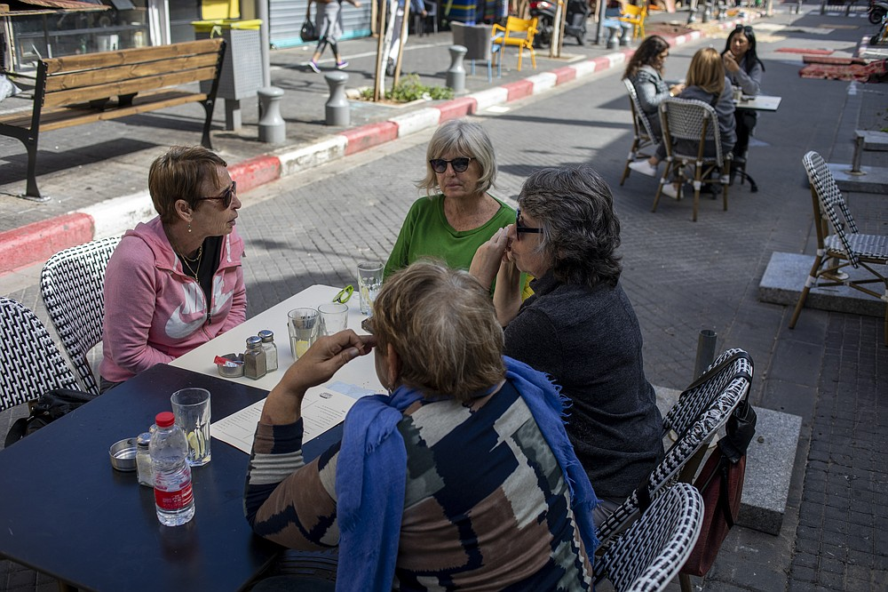 People eat in a restaurant as restrictions are eased following months of government-imposed shutdowns, in Tel Aviv, Israel, Sunday, March 7, 2021. Israel reopened most of its economy Sunday as part of its final phase of lifting coronavirus lockdown restrictions, some of them in place since September. (AP Photo/Ariel Schalit)