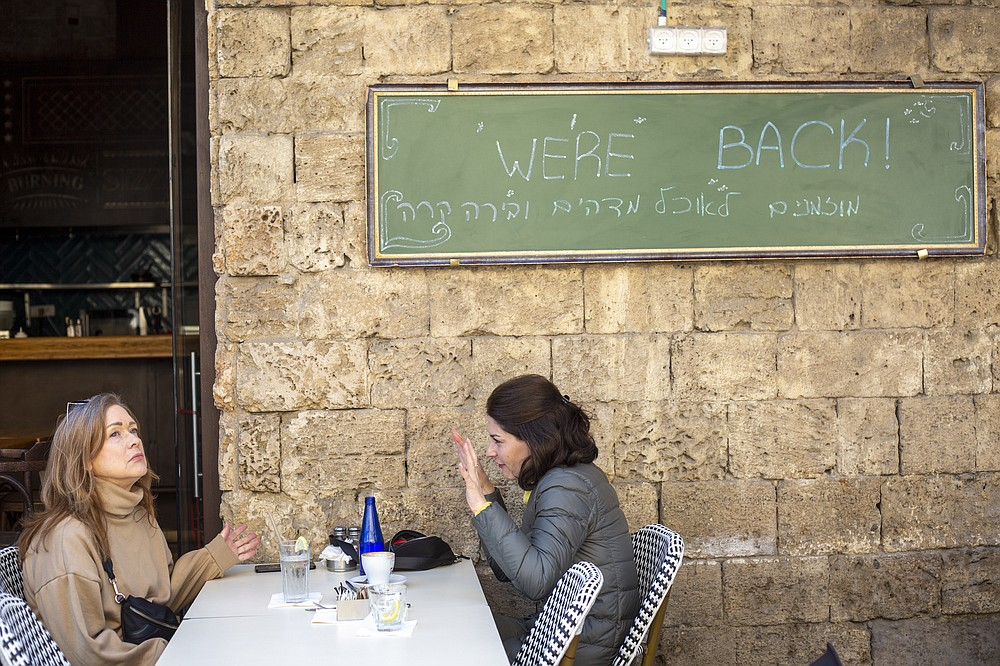 Women sit in a restaurant as restrictions are eased following months of government-imposed shutdowns, in Tel Aviv, Israel, Sunday, March 7, 2021. Israel reopened most of its economy Sunday as part of its final phase of lifting coronavirus lockdown restrictions, some of them in place since September. The sign says you'r invited for amazing food and cold beer. (AP Photo/Ariel Schalit)