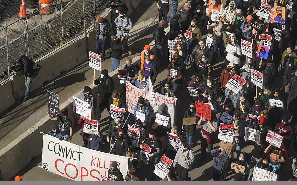 EDS NOTE: OBSCENITY - Hundreds of demonstrators march through Minneapolis following protests near the Hennepin County Government Center, Monday, March 8, 2021, in Minneapolis where the trial for former Minneapolis police officer Derek Chauvin began with jury selection. Chauvin is charged with murder in the death of George Floyd during an arrest last May in Minneapolis. (AP Photo/Jim Mone)