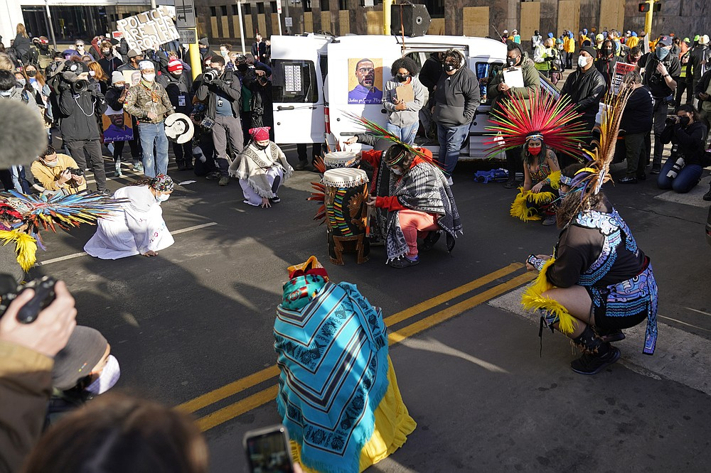 Dancers in native dress take part in a ceremony outside the Hennepin County Government Center, Monday, March 8, 2021, in Minneapolis where the trial for former Minneapolis police officer Derek Chauvin began with jury selection. Chauvin is charged with murder in the death of George Floyd during an arrest last May in Minneapolis. (AP Photo/Jim Mone)