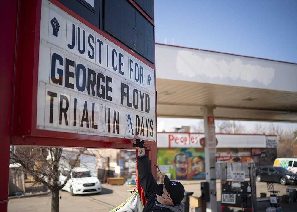 """Billy Briggs, who lives just 170 steps from where George Floyd was killed, created and maintains the countdown sign at the gas station on the corner of George Floyd Square in Minneapolis, Minn. On Sunday, the eve of the trial date, he updated it to """"1"""". (Jeff Wheeler /Star Tribune via AP)"""