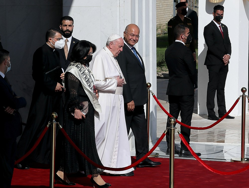 Pope Francis, center, walks with Iraqi President Barham Salih towards his plane upon concluding his visit to Iraq at Baghdad airport, Iraq, Monday, March 8, 2021. Pope Francis left Baghdad on Monday after three days of the historic whirlwind tour of Iraq that sought to bring hope to the country's marginalized Christian minority with a message of coexistence, forgiveness and peace. (AP Photo/Khalid Mohammed)