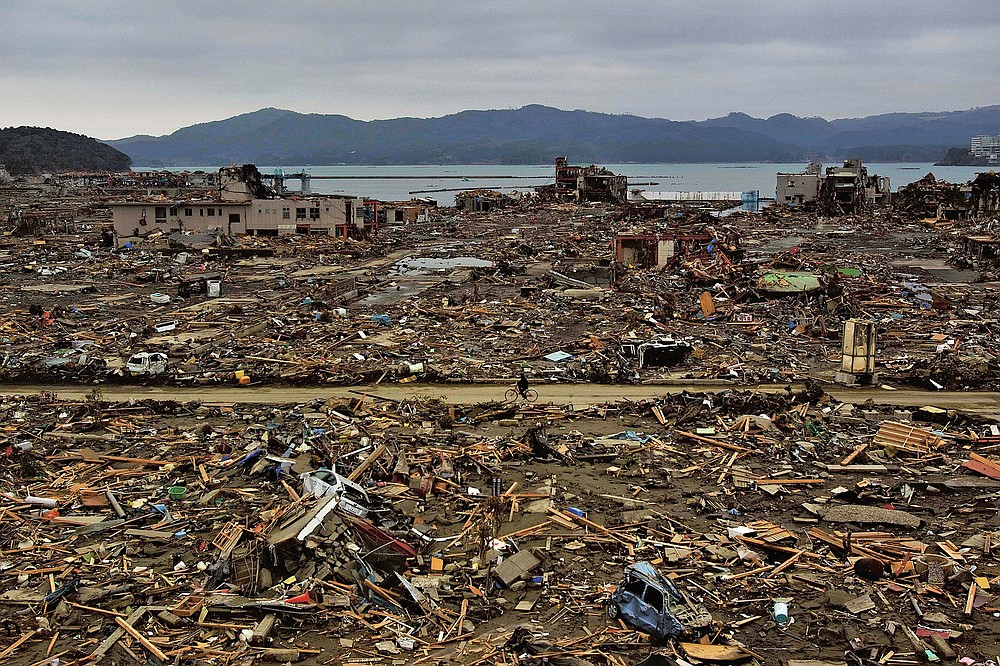 CORRECTION DATE - In this file photo dated March 15, 2011, a survivor of the earthquake and tsunami rides a bicycle through the flat city of Minamisanriku in northeastern Japan four days after the tsunami.  (AP Photo / David Guttenfelder, file)