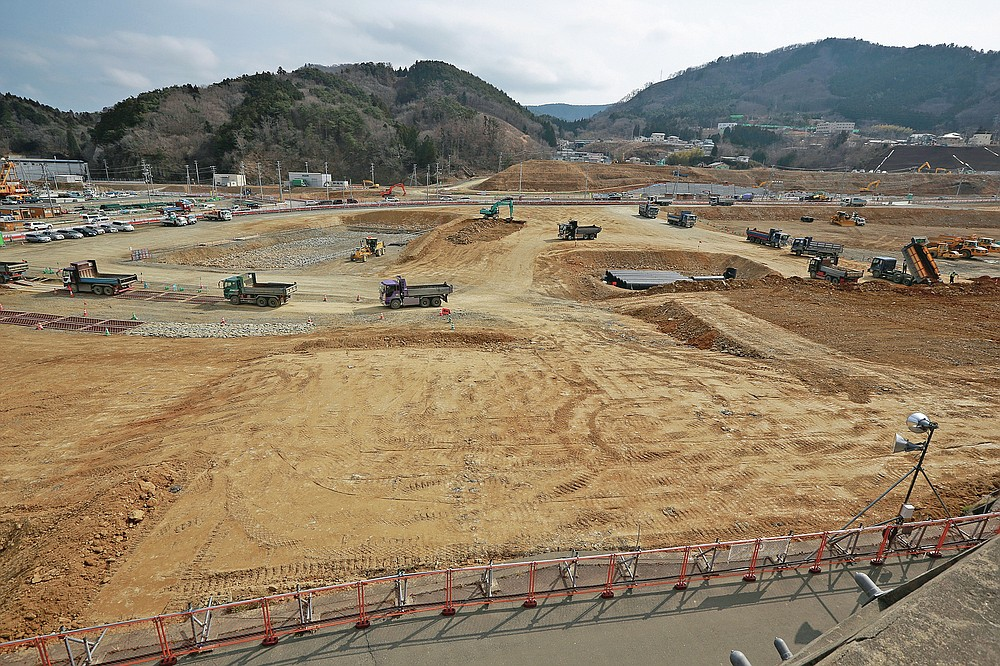 In this file photo dated March 5, 2016, trucks are queuing to dump soil in the tsunami and the earthquake-devastated city of Onagawa, Miyagi Prefecture, northern Japan.  (AP Photo / Eugene Hoshiko, File)