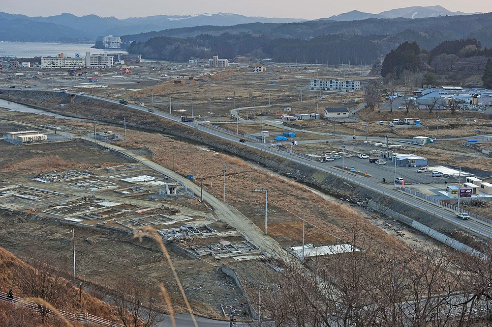 In this file photo dated February 23, 2012, almost a year after the March 11, 2011 tsunami, vehicles are driving through the ruins of the flat city of Minamisanriku in Miyagi Prefecture in northern Japan.  (AP Photo / David Guttenfelder, file)