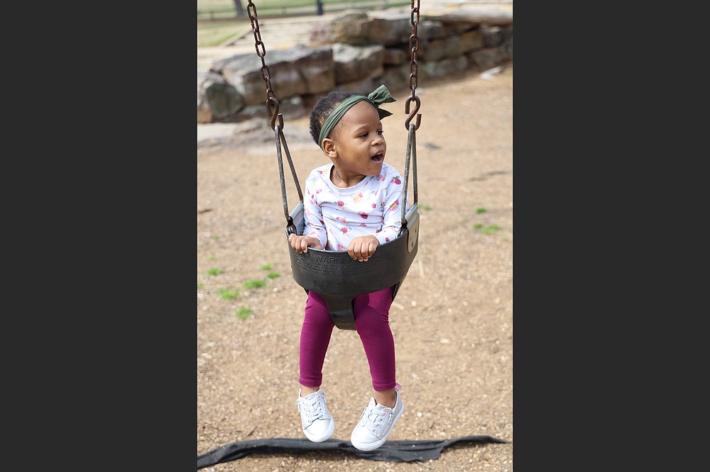 Mauria, 2, a child awaiting adoption, plays on the swing at Little Rock's War Memorial Park. The covid-19 pandemic presented a challenge to agencies that help Mauria and other wards of the state find forever families. (Special to the Democrat-Gazette/Dwain Hebda)