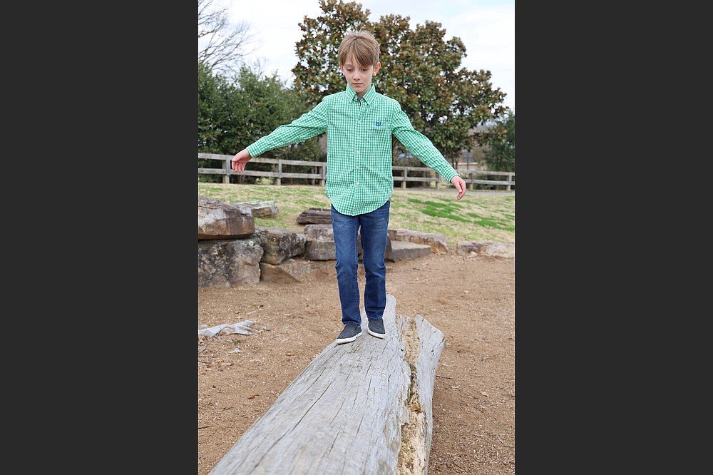Isaiah, 9, a child awaiting adoption, walks a log at War Memorial Park. Statistics from the Arkansas Department of Human Services' Division of Children and Family Services show that the number of children in foster care at the end of 2020 grew to 4,663, with average discharges to permanency lowered by more than 40 kids per month and discharges to reunification down 14 children per month, compared to 2019. Adoptions were also down year over year. (Special to the Democrat-Gazette/Dwain Hebda)