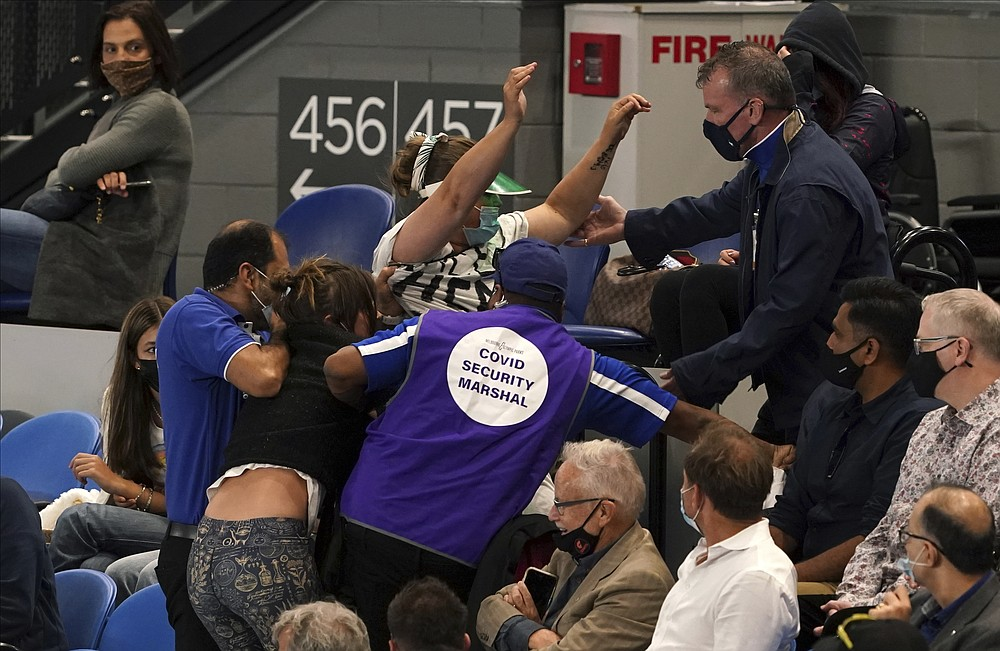FILE - Women are ejected by security during the men's singles final match between Serbia's Novak Djokovic and Russia's Daniil Medvedev on Rod Laver Arena at the Australian Open tennis championship in Melbourne, Australia, in this Sunday, Feb. 21, 2021, file photo. (AP Photo/Mark Dadswell)