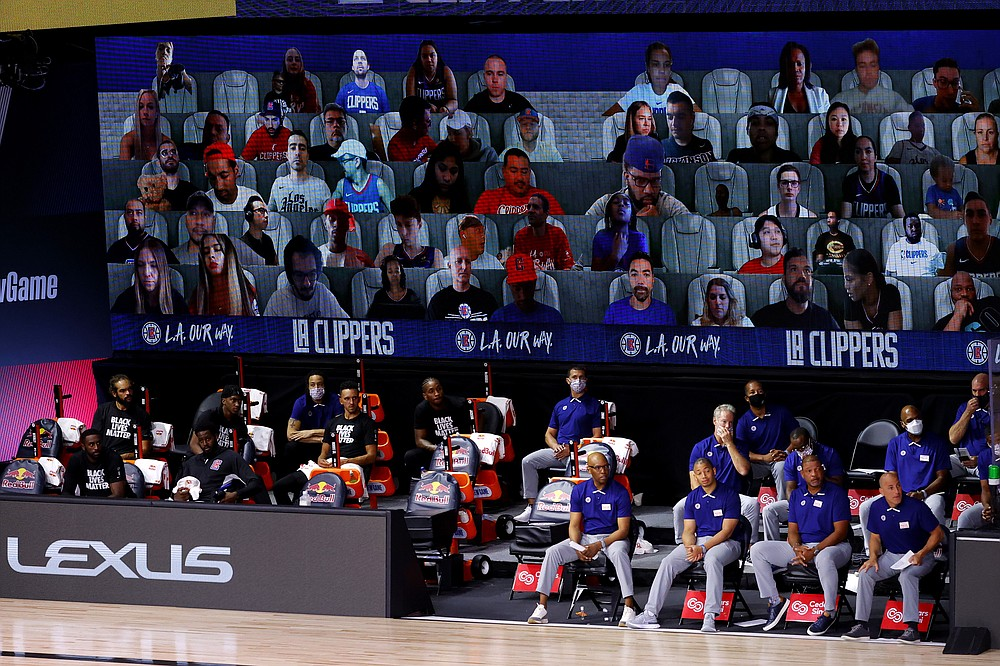 FILE - This Tuesday, Aug. 4, 2020, file photo shows a view of the Los Angeles Clippers bench and fans on a screen during the first half of an NBA basketball game against the Phoenix Suns in Lake Buena Vista, Fla. The entire essence of sports as we know them changed in subtle, if fundamental, ways during the past 12 months because of restrictions on crowds. (Kevin C. Cox/Pool Photo via AP, File)
