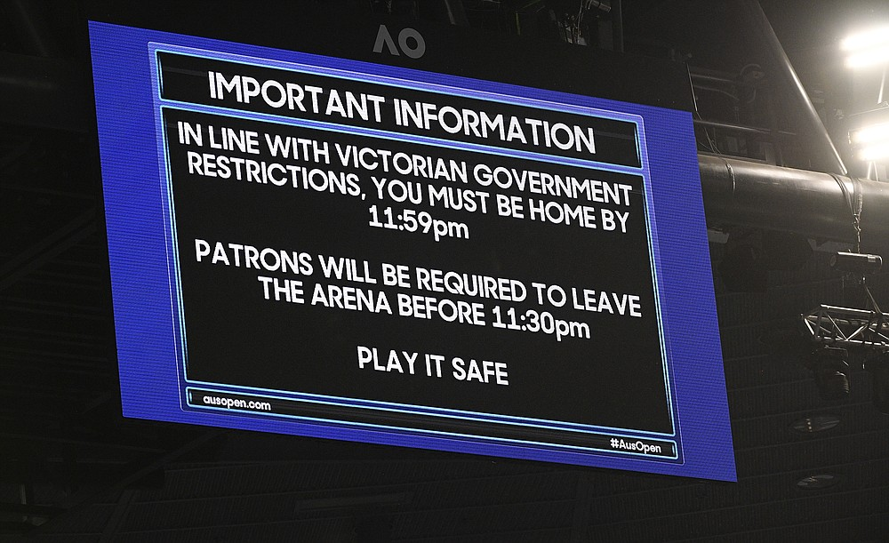 FILE - An electronic signboard on Rod Laver Arena reminds patrons about the lockdown start time during the third round match between Serbia's Novak Djokovic and United States' Talyor Fritz at the Australian Open tennis championship in Melbourne, Australia, in this Friday, Feb. 12, 2021, file photo. Sports amid the pandemic became a whole different sort of spectacle, especially when it came to spectators — often with zero, sometimes with some and, in at least one instance at a Grand Slam tennis tournament, starting a match with fans in the seats yet finishing it with none present. (AP Photo/Andy Brownbill, File)