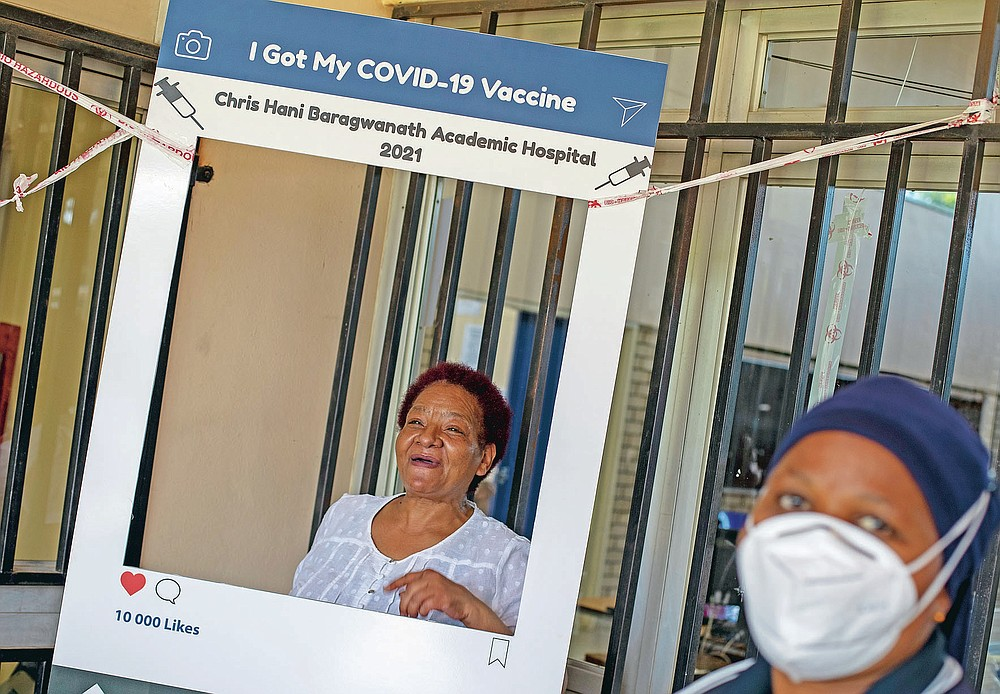 """Maggie Sedidi, a 59-year-old nurse at Soweto's Chris Hani Baragwanath hospital, poses for a photo taken by a colleague after receiving her dose of the Johnson & Johnson COVID-19 vaccine from a health staff member at a vaccination center in Soweto, South Africa, Friday, March 5, 2021. Sedidi is optimistic: """"By next year, or maybe the year after, I really do hope that people will be able to begin returning to normal life."""" (AP Photo/Themba Hadebe)"""
