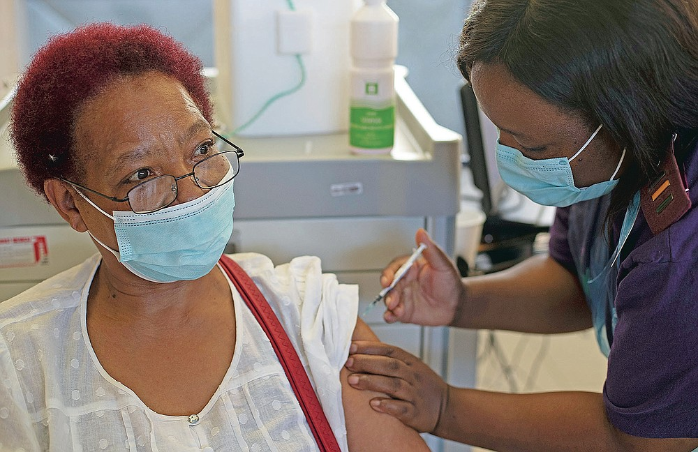 """Maggie Sedidi, a 59-year-old nurse at Soweto's Chris Hani Baragwanath hospital, receives the Johnson & Johnson COVID-19 vaccine from a health staff member at a vaccination center in Soweto, South Africa, Friday, March 5, 2021. Sedidi is optimistic: """"By next year, or maybe the year after, I really do hope that people will be able to begin returning to normal life."""" (AP Photo/Themba Hadebe)"""