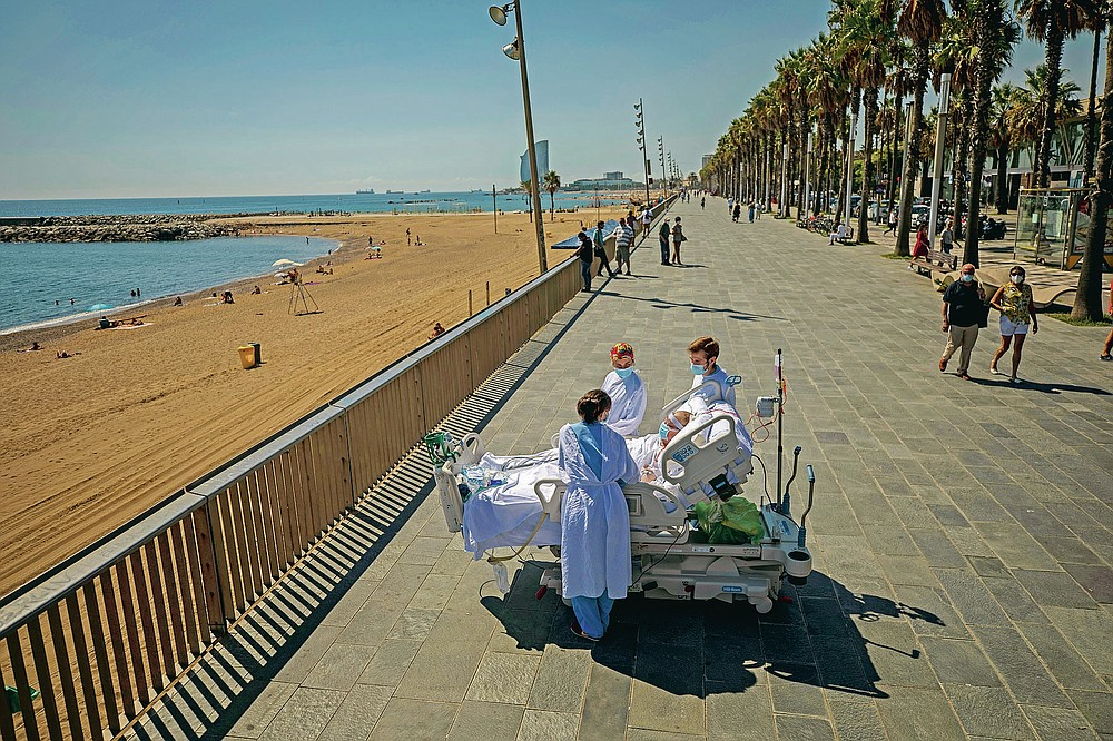 """FILE - In this Sept. 4, 2020, file photo, Francisco Espana, 60, is surrounded by members of his medical team as he looks at the Mediterranean sea from a promenade next to the """"Hospital del Mar"""" in Barcelona, Spain. Francisco spent 52 days in the Intensive Care unit at the hospital due to coronavirus, but today he was allowed by his doctors to spend almost ten minutes at the seaside as part of his recovery therapy. (AP Photo/Emilio Morenatti, File)"""