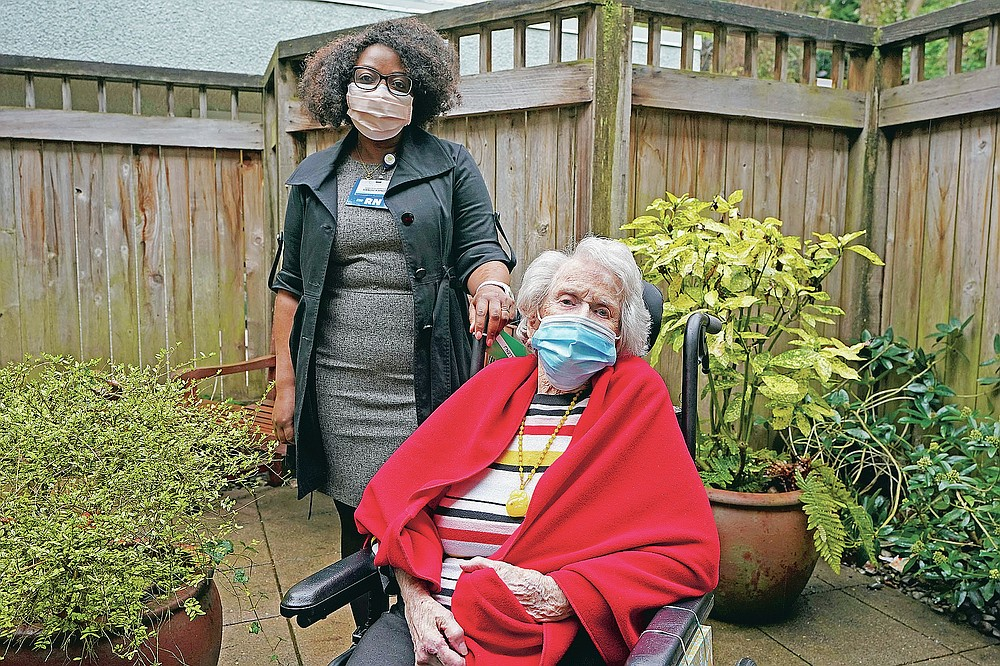 Sangu Kande, left, a nurse at Queen Anne Healthcare, a skilled nursing and rehabilitation facility in Seattle, poses for a photo, Friday, March 5, 2021, with Jean Allen, 96, one of the patients Kande cared for during the past year. Allen was infected and recovered from coronavirus. But 19 of her fellow residents and two beloved staff members died. The deaths trailed off, but the isolation and boredom continue. (AP Photo/Ted S. Warren)