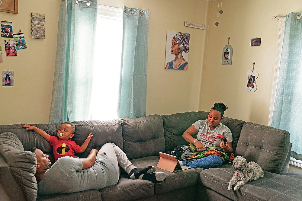Darelyn Maldonado, 12, right, sits on the couch with her dog, Lisa, stepfather, Steven Depina, left, and 16-month-old brother, Elijah, at their home in Pawtucket, R.I., Wednesday, March 3, 2021. Maldonado, a seventh grade student, has been out of in person school for a year since the pandemic began. She feels like she's lost friends over the past year, has missed out on playing softball which she loves and just wants her life to go back to normal. (AP Photo/David Goldman)
