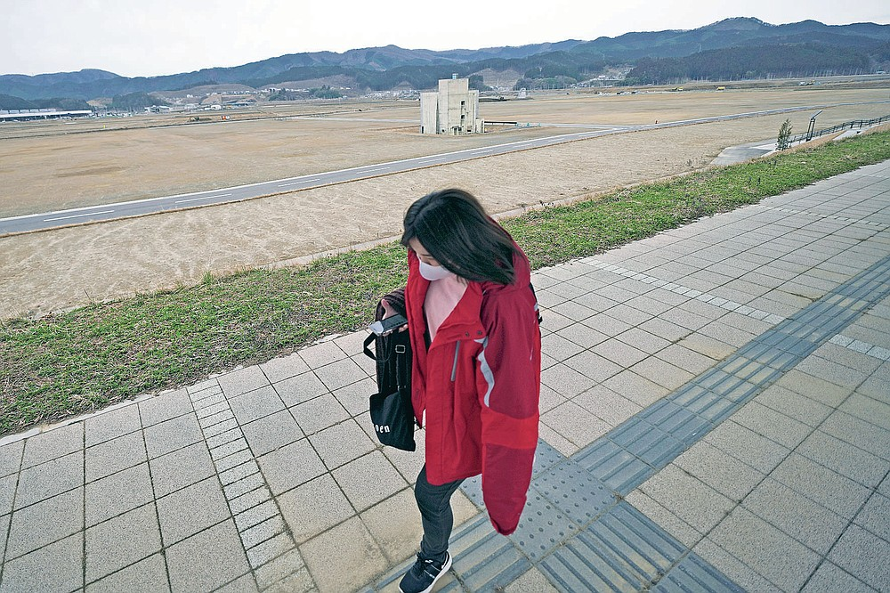 A woman walks past the ruin of a building destroyed by the 2011 tsunami in Rikuzentakata, Iwate Prefecture, Friday, March 5, 2021. In Rikuzentakata more than 1,700 people died by the March 11, 2011 disaster. (AP Photo/Eugene Hoshiko)