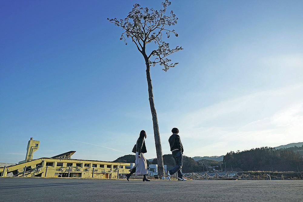 """A man and a woman walk near a replica of a lone pine tree that initially survived the 2011 tsunami that flattened the surrounding coastal forest, in Rikuzentakata, Iwate Prefecture, northern Japan Thursday, March 4, 2021. The tree, which eventually died of seawater exposure, was known as the """"Miracle Pine,"""" and townspeople treated, reinforced and then preserved it as a memorial and symbol of hope for the region. (AP Photo/Eugene Hoshiko)"""