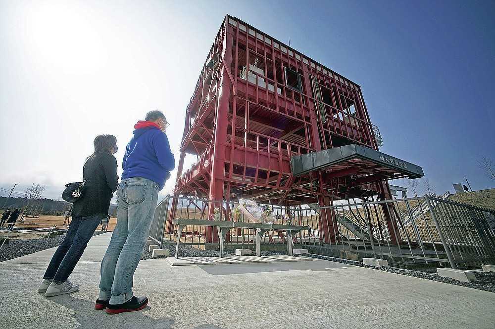 Visitors look at the skeleton of the disaster prevention headquarters building, where 43 workers died as the March 11, 2011 tsunami washed over it, in Minamisanriku, Miyagi Prefecture, northern Japan, Saturday, March 6, 2021. The three-story building is one of legacies that still stand in northern Japan's coastal towns, 10 years after the earthquake and tsunami that killed more than 18,000 people. (AP Photo/Eugene Hoshiko)