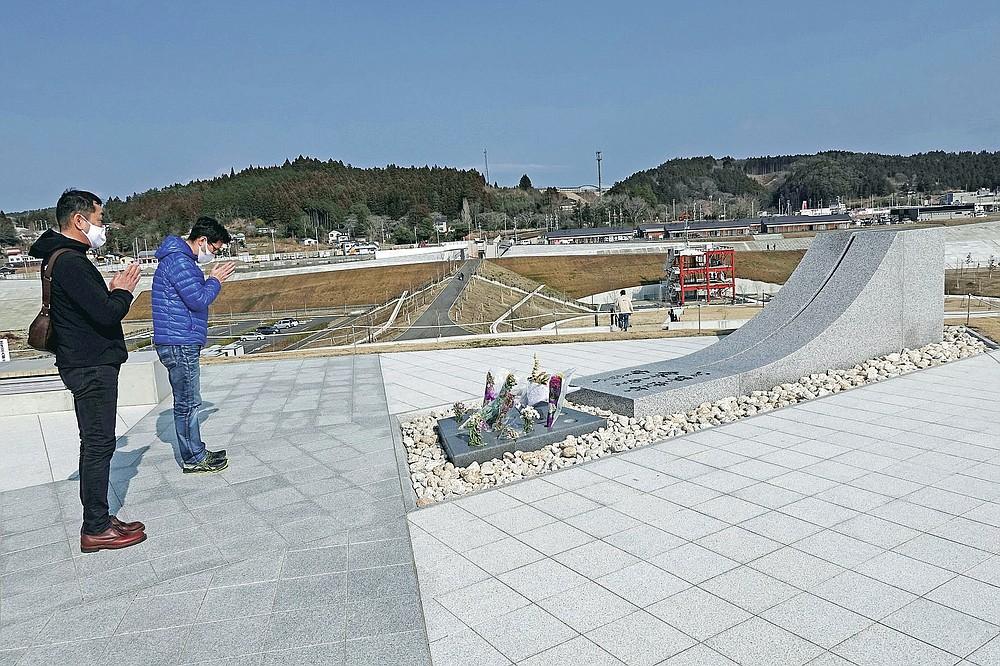 Visitors pray for the victims of the 2011 tsunami disaster at the Minamisanriku Memorial Park of Earthquake Disaster in Minamisanriku, Miyagi Prefecture, northern Japan, Saturday, March 6, 2021. The disaster marks the 10th-year anniversary on March 11, 2021. (AP Photo/Eugene Hoshiko)