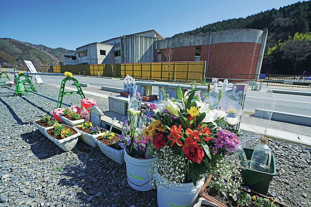 Offering flowers are placed at former Okawa Elementary School where 74 children along with 10 teachers died because of a botched evacuation when the tsunami hit on March 11, 2011, in Ishinomaki, Miyagi Prefecture, northern Japan Sunday, March 7, 2021. (AP Photo/Eugene Hoshiko)