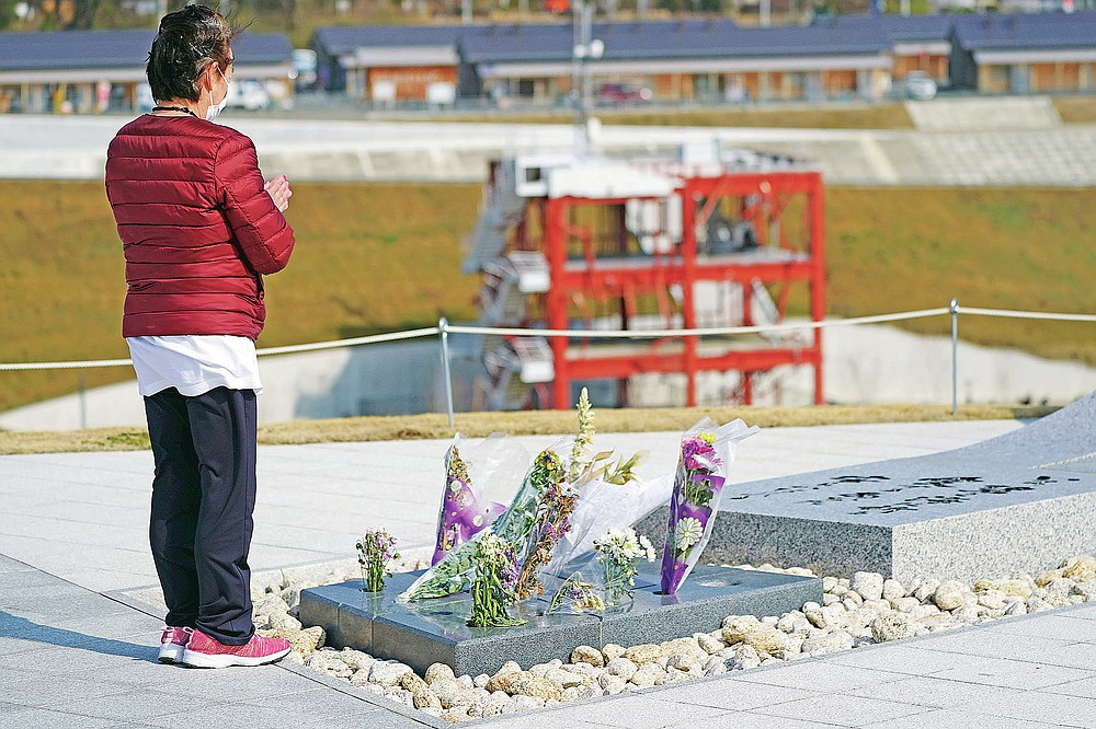 A visitor prays for the victims of the 2011 tsunami near the skeleton of the tsunami-damaged disaster prevention headquarters, where 43 workers died as the tsunami washed over it, in Minamisanriku, Miyagi Prefecture, northern Japan, Saturday, March 6, 2021. The three-story building is one of legacies that still stand in northern Japan's coastal towns, 10 years after the earthquake and tsunami that killed more than 18,000 people. (AP Photo/Eugene Hoshiko)