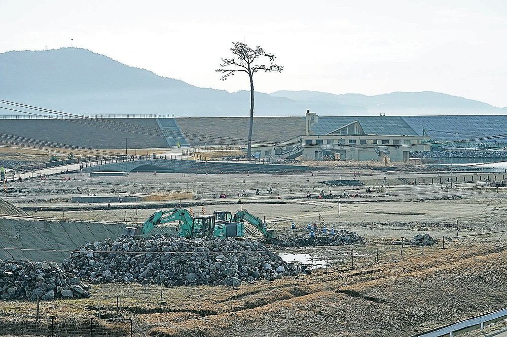 """A replica of a lone pine tree that initially survived the 2011 tsunami that flattened the surrounding coastal forest, stands in Rikuzentakata, Iwate Prefecture, northern Japan Thursday, March 4, 2021. The tree, which eventually died of seawater exposure, was known as the """"Miracle Pine,"""" and townspeople treated, reinforced and then preserved it as a memorial and symbol of hope for the region. (AP Photo/Eugene Hoshiko)"""