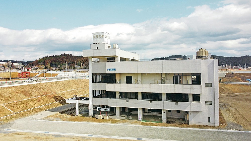 Takano kaikan building stands with a blue marker where the water rose when 2011 deadly tsunami hit the region in Minamisanriku, northern Japan, March 6, 2021. When the tsunami struck the town, around 300 senior citizens evacuated to a room on the top floor and a machinery room on the roof to survived. (AP Photo/Haruka Nuga)