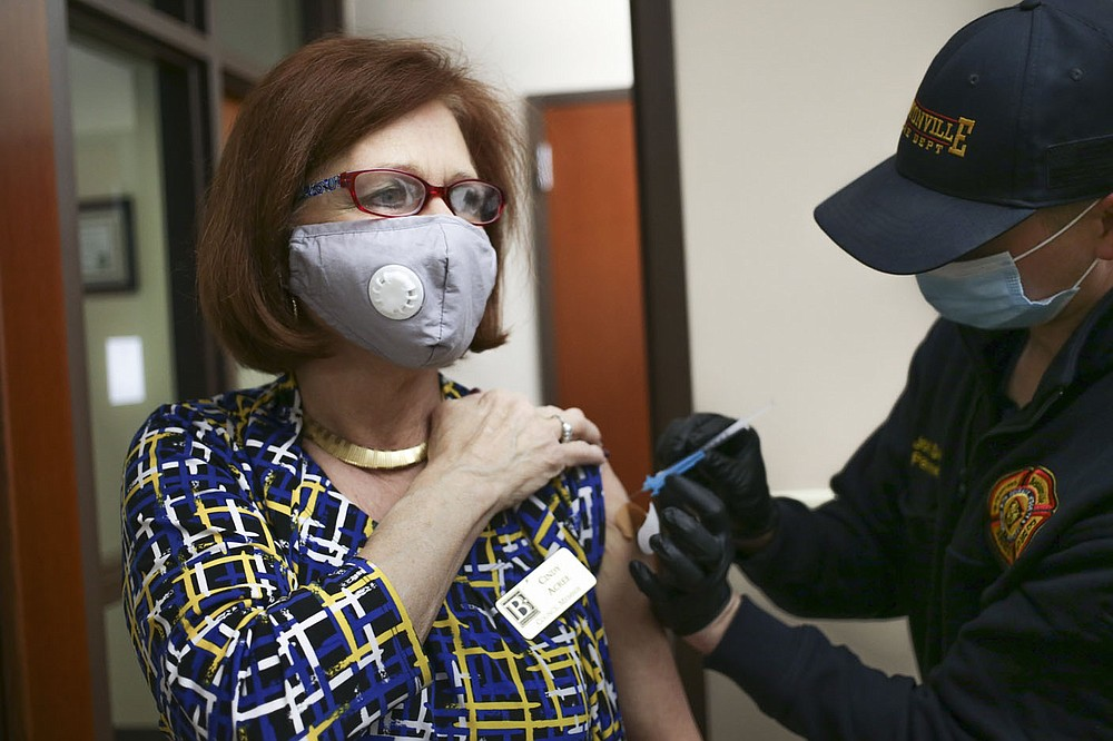 Bentonville Fire Department Paramedic Josh Davis (right) administers a covid-19 vaccine to City Council member Cindy Acree (left), Friday at the Bentonville City Hall in Bentonville. The Bentonville Fire Department administered 150 vaccines to city employees at various city properties in Bentonville. Check out nwaonline.com/210312Daily/ for today's photo gallery.  (NWA Democrat-Gazette/Charlie Kaijo)