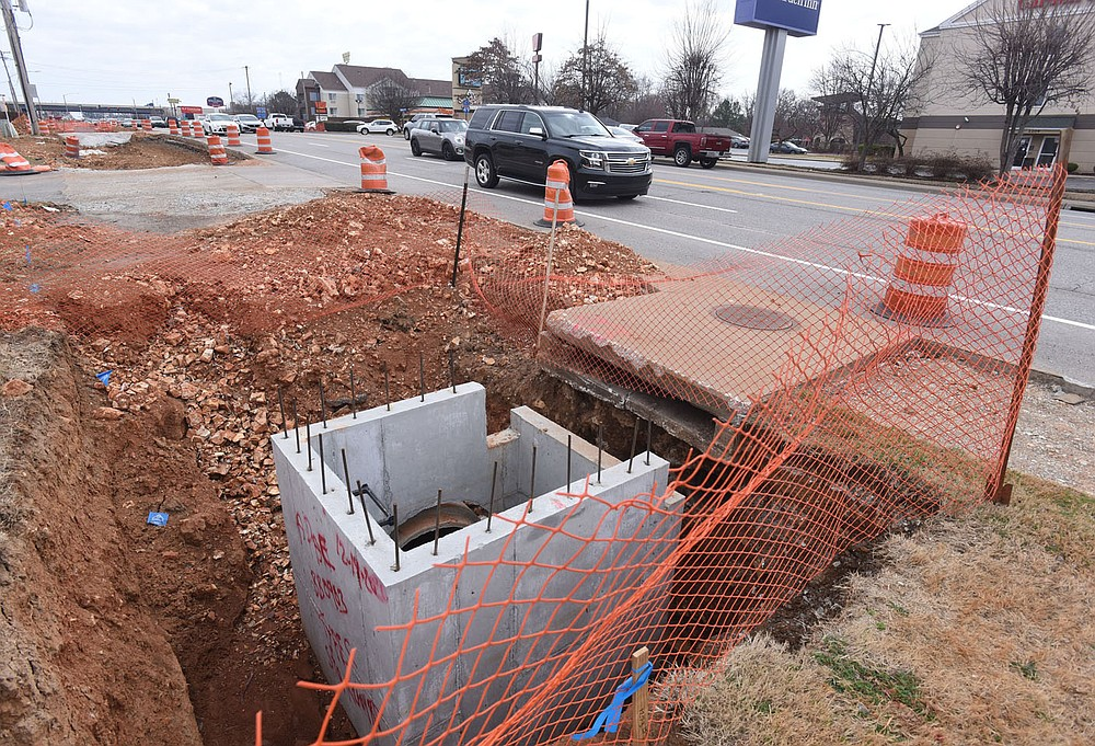 Traffic moves Tuesday March 9 2021 near drainage work along Southeast Walton Boulevard. (NWA Democrat-Gazette/Flip Putthoff)