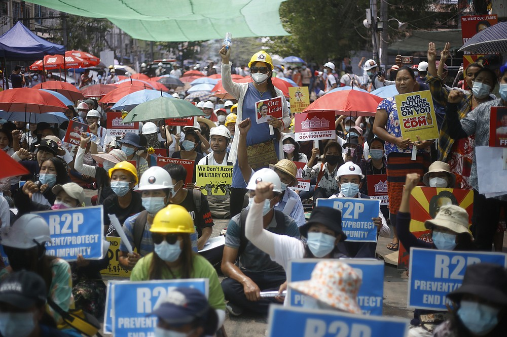 Anti-coup protesters shout slogans and hold pictures of the deposed leader Aung San Suu Kyi during a protest in Yangon, Myanmar, Saturday, March 13, 2021. Security forces in Myanmar on Saturday again met protests against last month's military takeover with lethal force, killing at least four people by shooting live ammunition at demonstrators. (AP Photo)